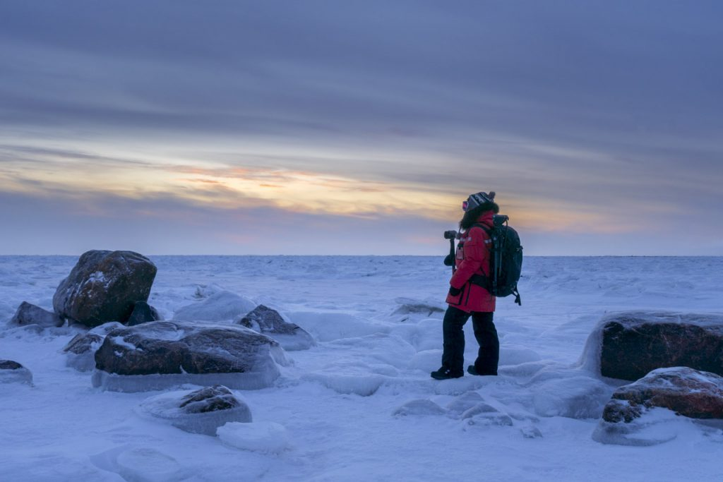 Deb, a travel blogger, standing in the middle of snow for as far as the eye can see