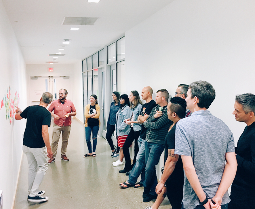The team gathers in the hallway to create a Post-it timeline on the wall
