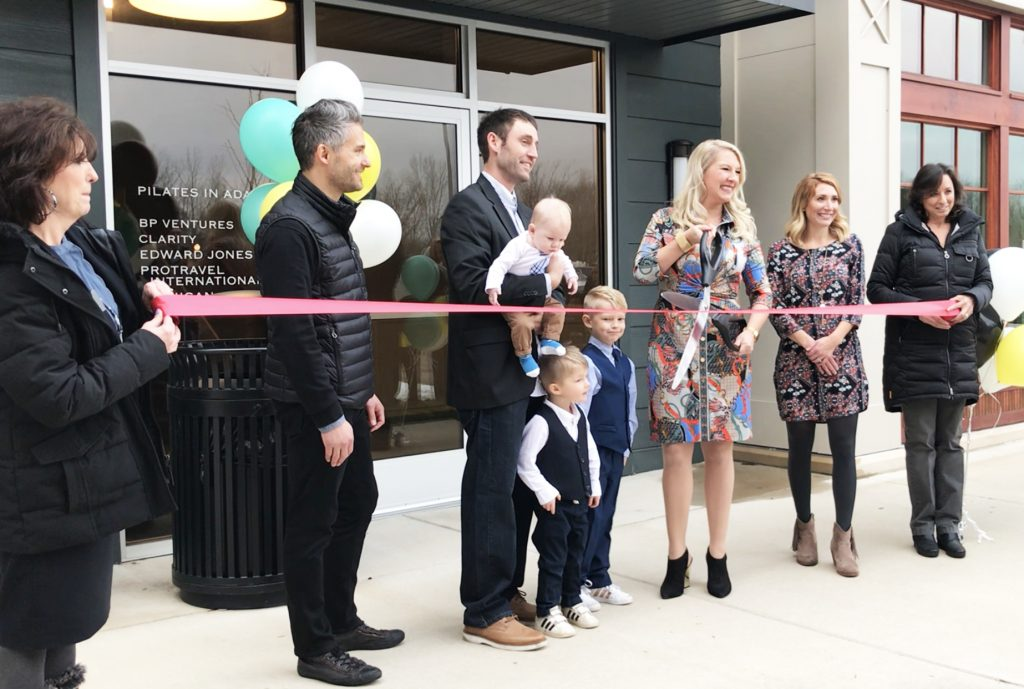 Ashlea Souffrou holds the scissors at the SxanPro ribbon cutting, surrounded by family and colleagues