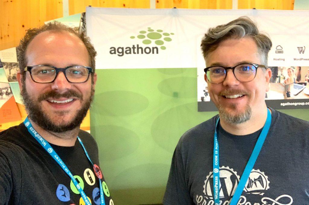 Morgan & Joel posing in front of their sponsor booth at WordCamp GR 2019